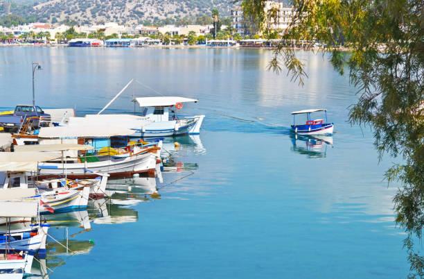landscape of traditional fishing boats reflected on sea at Eretria Euboea Greece stock photo