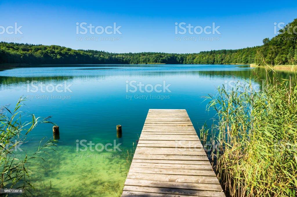 An einem See mit Bäumen und blauen Himmel Landschaft – Foto