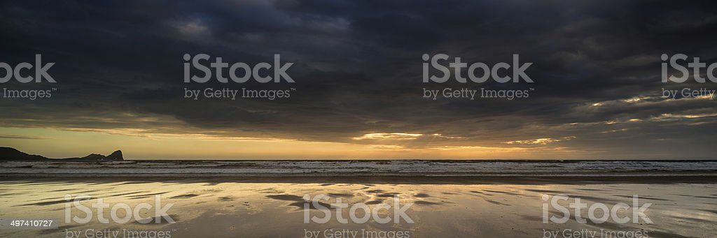 Landscape panorama Rhosilli Bay beach at sunset with moody sky stock photo