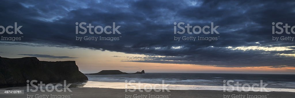 Landscape panorama Rhosilli Bay beach at sunset with moody sky royalty-free stock photo