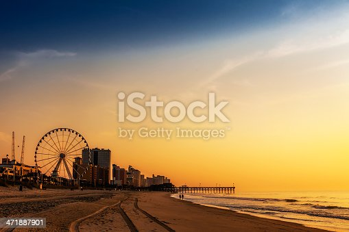 A royalty free DSLR action photo of dramatic colors as they emblazon the sky at a resort beach during sunrise/sunset. Cast in silhouette are a ferris wheel, hotel condominiums, beachcombers, and a long seaside dock.