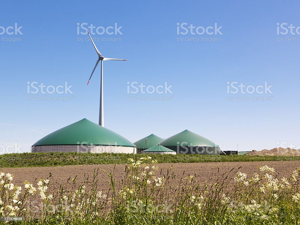 Landscape shot of a biogas plant and a wind turbine stock photo