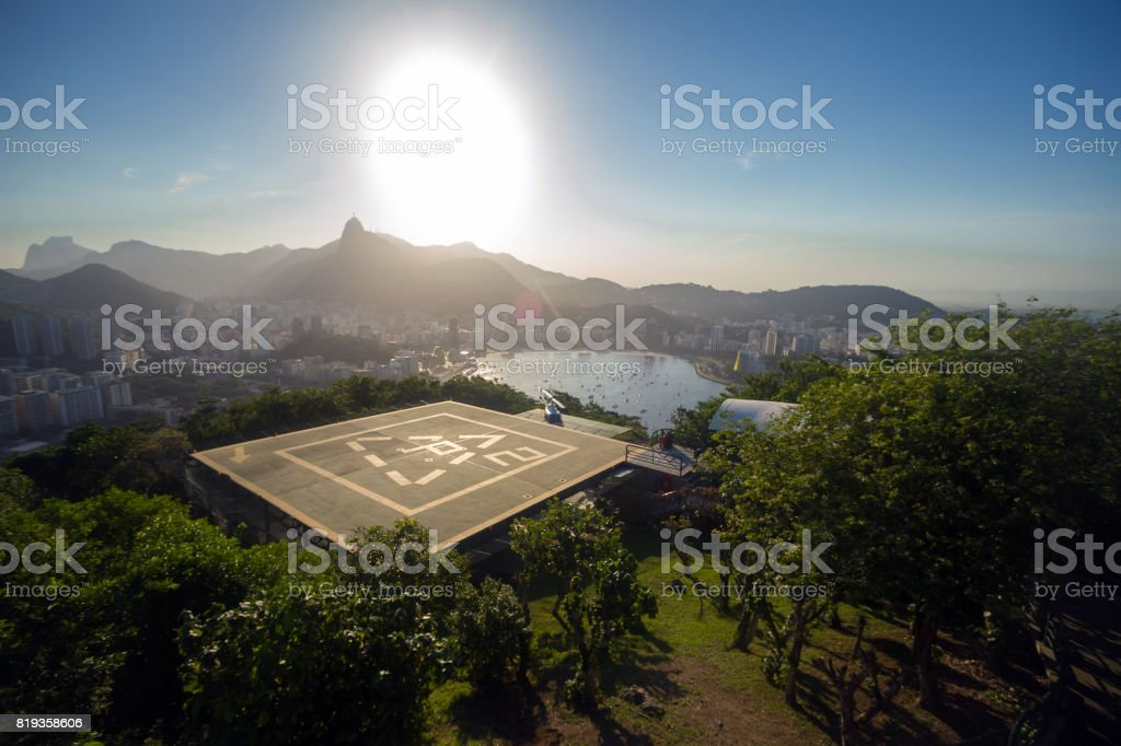 Landscape view from the Sugarloaf mountain on the Guanabara bay, Corcovado mountain with Crist the Redeemer, some hills and mountains and heliport for touristic flights. stock photo