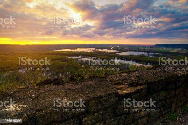 Photo of Landscape view from Wyalusing State Park by capture sunrise or sunset over the lake in cloudy day with old brick wall at foreground.