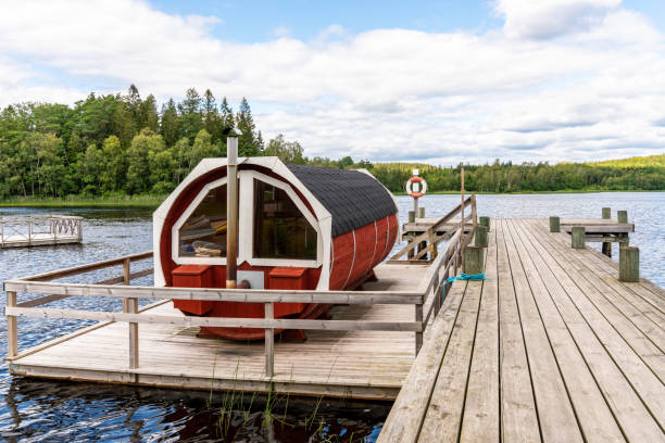 Landscape view of a traditional Scandinavian water floating red wooden sauna next to a jetty. stock photo