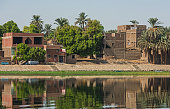 View across large wide river Nile in Egypt at Edfu through rural countryside landscape with african houses on riverbank