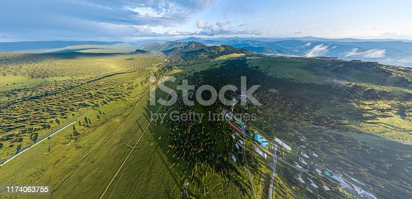 Panorama of the mountains with small village  in Altai on a summer clear day. A landscape view of beautiful fresh green field   and  Altai mountain background.  Panoramic view of beautiful green field