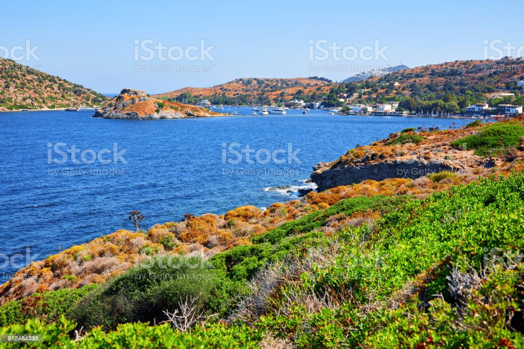 landscape view of Bodrum Gumusluk (Myndos) bay and rabbit island in Turkey from an hill covered with thorn bushes and wild plants stock photo
