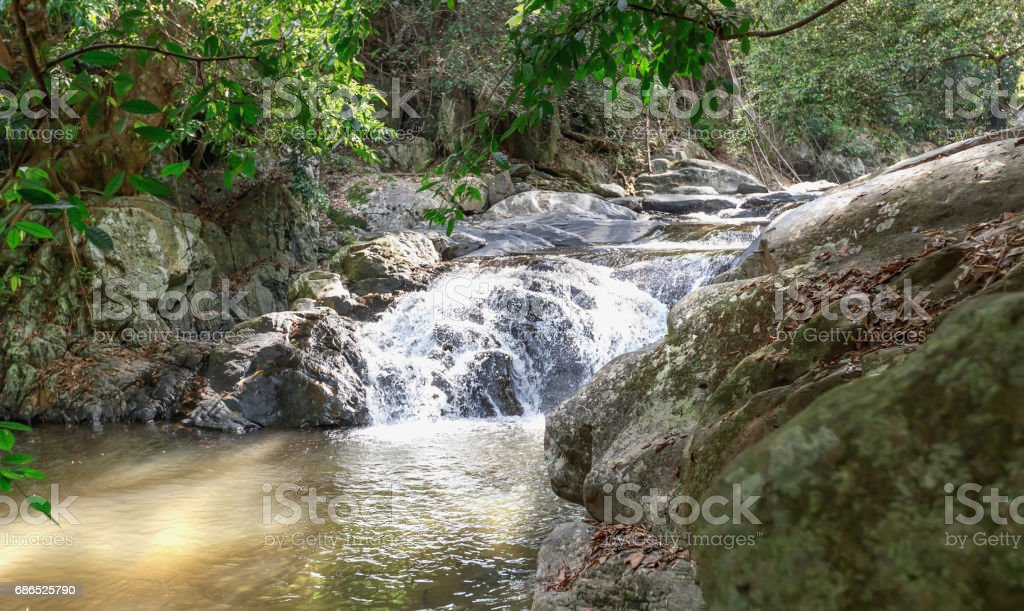 Landscape view of cascade and water stream with the sunbeam in summer, Thailand, trekking and hiking concept. zbiór zdjęć royalty-free