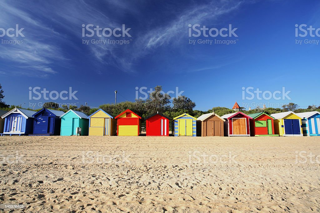 A landscape view of colorful beach huts in a row royalty-free stock photo