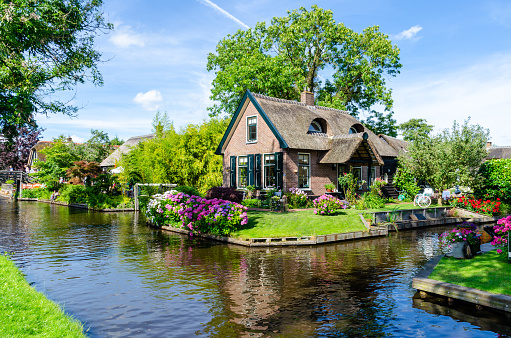 Giethoorn, Netherlands: Landscape view of famous Giethoorn village with canals and rustic thatched roof houses. The beautiful houses and gardening city is know as
