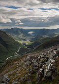 View of the valley of Glen Etive from the Stob Dubh peak, summit of the Buachaille Etive Beag, with Loch Etive in the background and rocks in the foreground. Highlands of Scotland. Munros. Hiking. Hill Walking.
