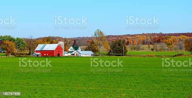 Photo of Landscape view of red Midwestern dairy farmhouse and land