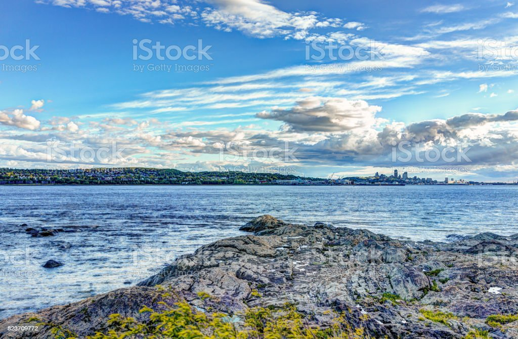 Landscape view of Saint Lawrence river from Ile D'Orleans, Quebec, Canada in summer with green plants, rocks and cityscape skyline of city and Levis town stock photo