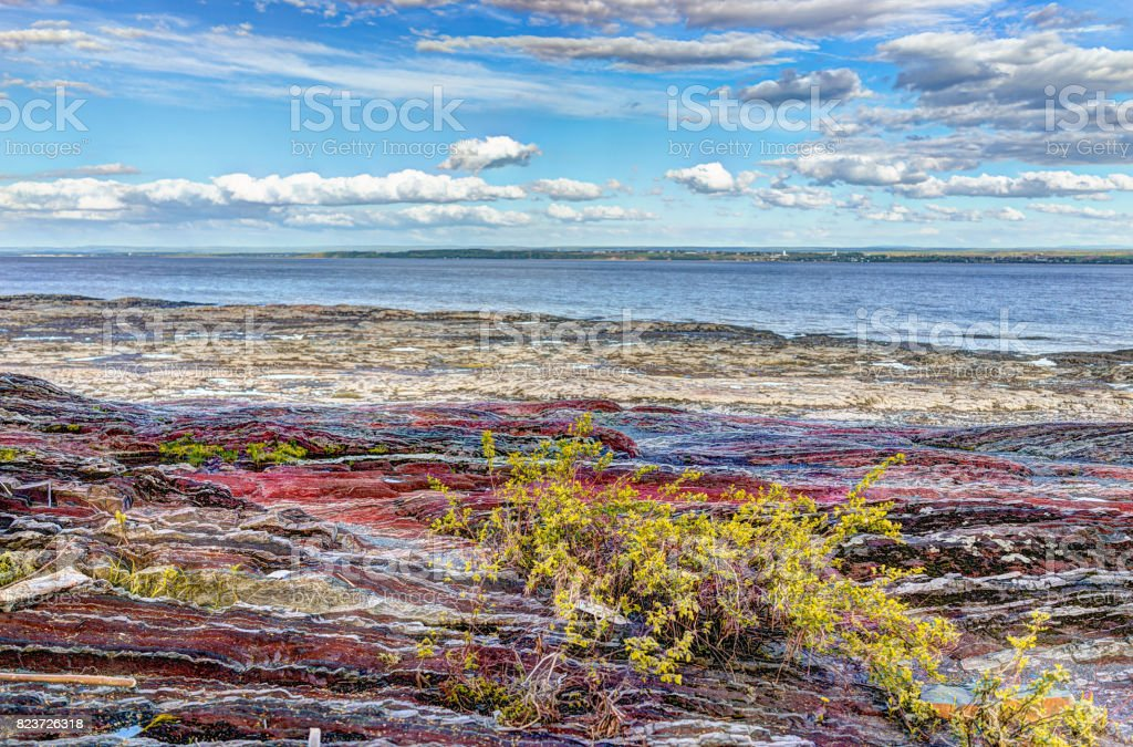 Landscape view of Saint Lawrence river from Ile D'Orleans, Quebec, Canada in summer with red rocks stock photo