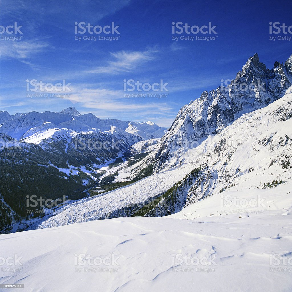 Landscape view of snow-covered mountains and woods in the valley royalty-free stock photo