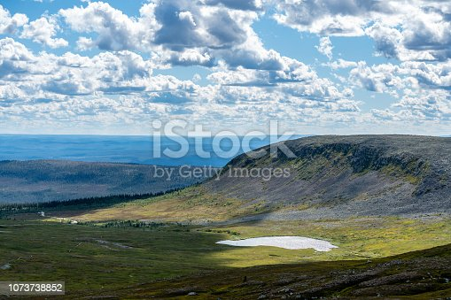 Beautiful sunny summer view of the Highlands in Northern Sweden, with a small lake in the valley and a bright cloudy and blue sky