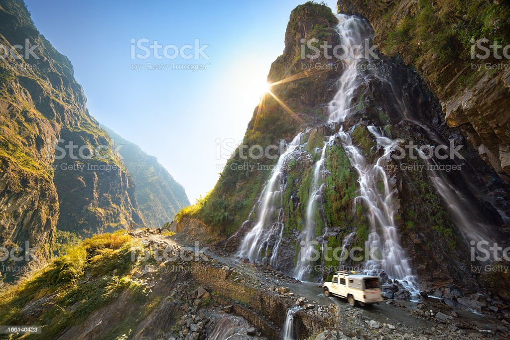 Landscape view of white truck going by roadside waterfall royalty-free stock photo