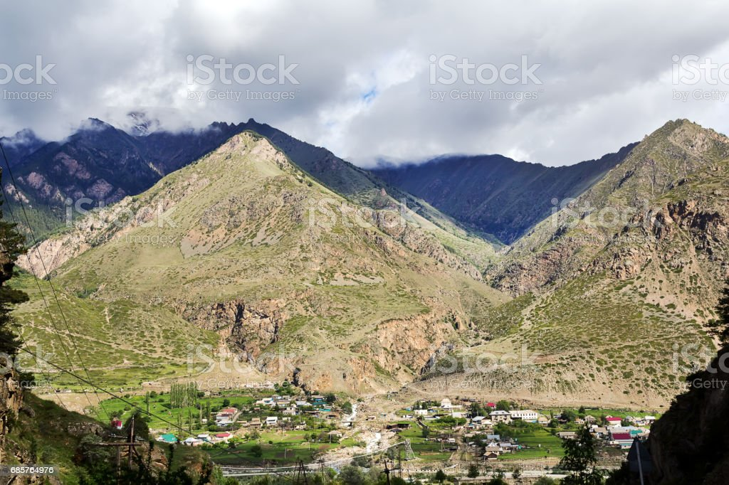 Landscape with a small village at the foot of mountains royaltyfri bildbanksbilder