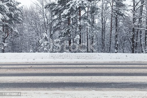 Landscape with an empty winter highway going through the forest