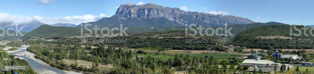Un paisaje con cielo azul, unas nubes y el macizo de la montaña de la Peña Montañesa en el Pirineo aragonés de español, como se ve en Ainsa, un pequeño, piedra, pueblo rural de la edad media - foto de stock
