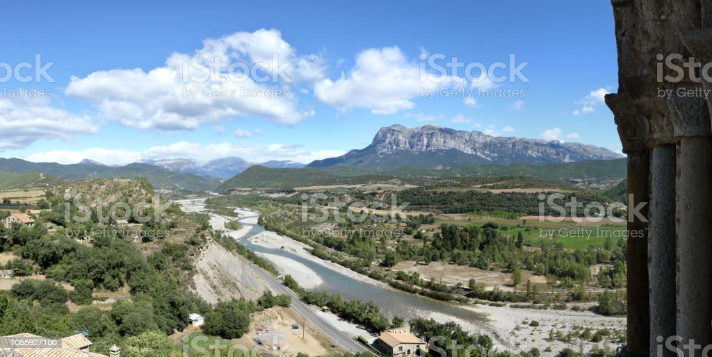 Un paisaje con cielo azul, unas nubes y el macizo de la montaña de la Peña Montañesa en el Pirineo aragonés de español, como se ve desde Ainsa campana de la torre, un pequeño, hecho piedra, pueblo rural de la edad media - foto de stock