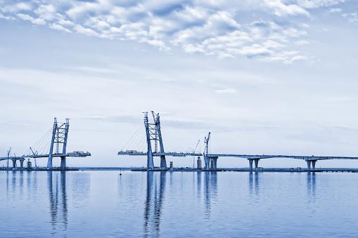 Monochrome toned landscape with clouds, sea and bridge construction