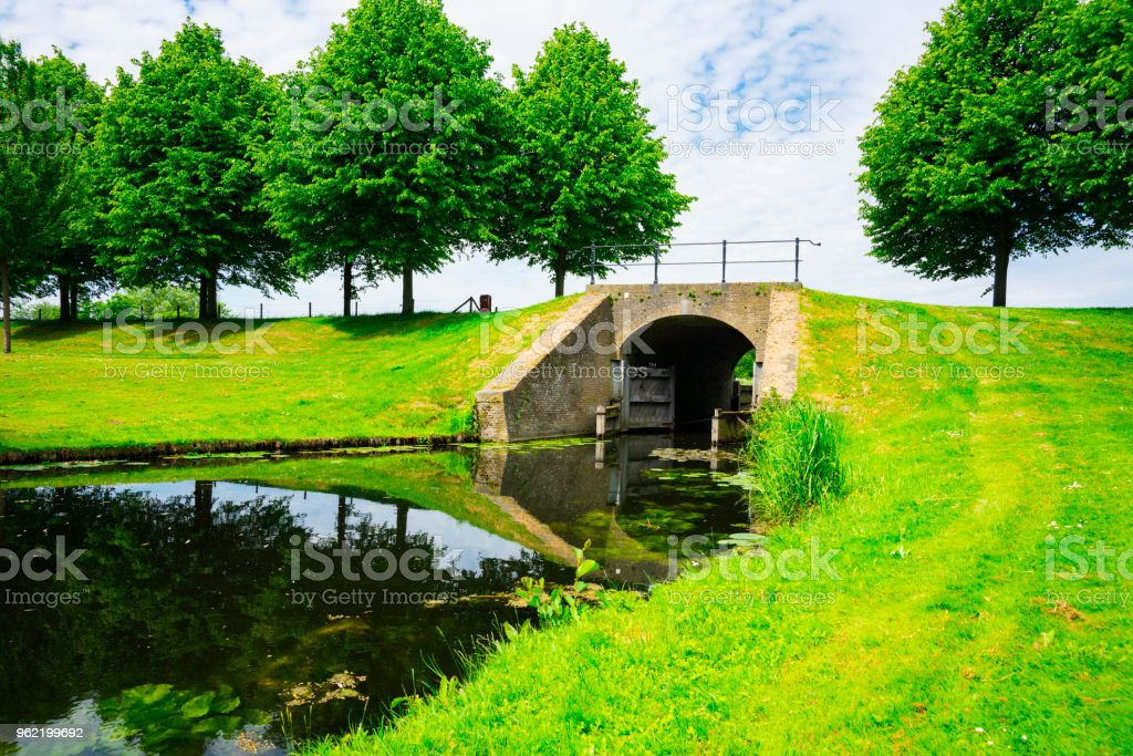 landscape with bridge, sluice, grass field in Klundert, the Netherlands stock photo