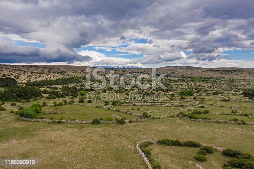 Aerial view of a scenic green landscape with stone walls, bushes and hills in the distance under a blue sky with white clouds, Krk Island, Primorje-Gorski Kotar County