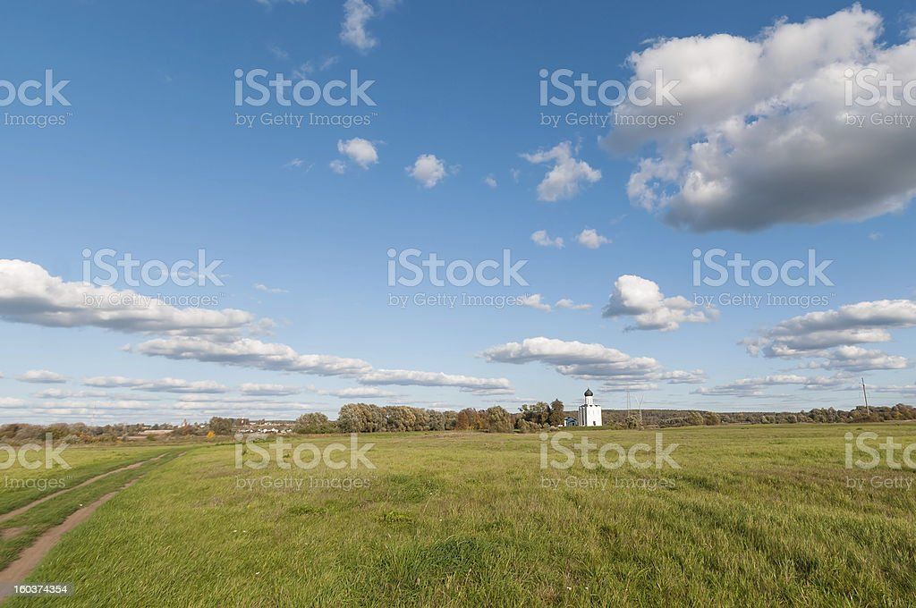Landscape with church, meadow and road against blue sky background royalty-free stock photo