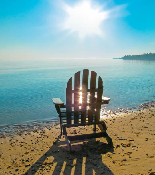 landschaft mit küste, wasser, sonne mit hellen sonnenstrahlen in den himmel und strand stuhl. - lake michigan strände stock-fotos und bilder