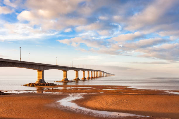 landscape with confederation bridge leading to prince edward island canada - prince edward island stock photos and pictures