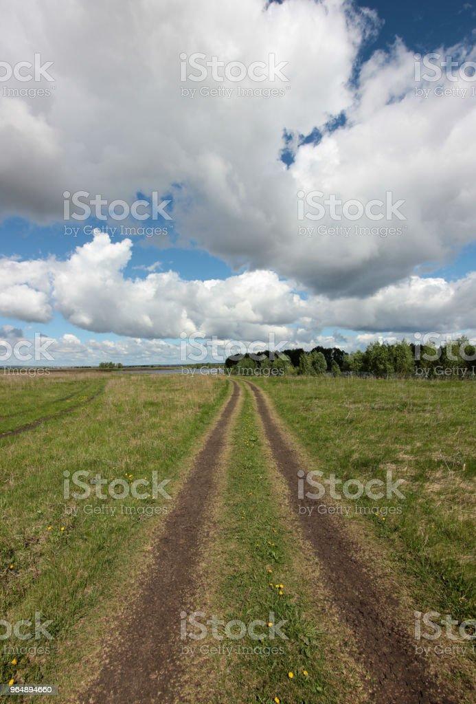 paisagem com estrada de terra em campo largo e nuvens baixas - Foto de stock de Azul royalty-free