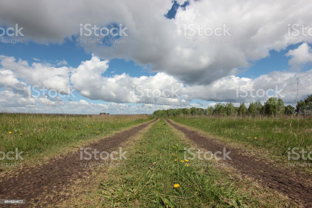 landscape with dirt road in wide field and low clouds royalty-free stock photo