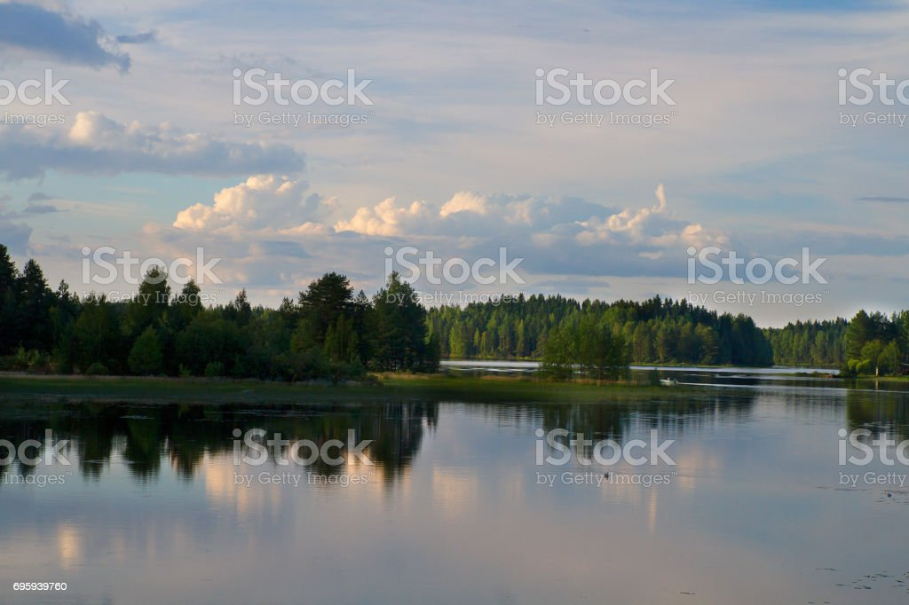 Landscape with finnish lake and forest in a summer day. Skyline and small clouds. стоковое фото
