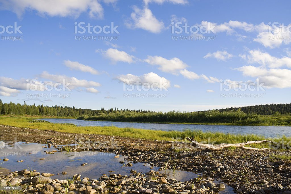 Landscape with log, river and clouds royalty-free stock photo