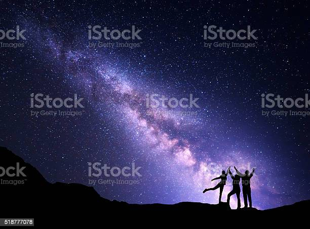 Photo of Landscape with Milky Way and silhouette of a happy family