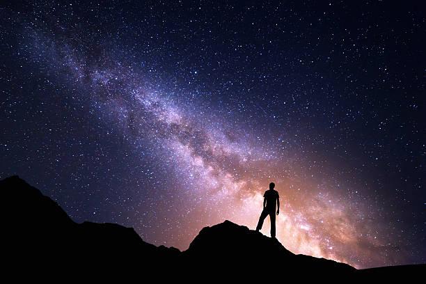 paysage avec la voie lactée et silhouette d'un homme heureux - astronomie photos et images de collection