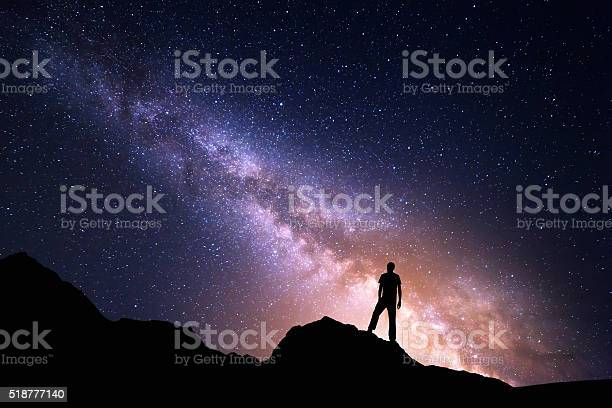 Photo of Landscape with Milky Way and silhouette of a happy man