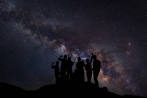 Landscape with milky way and silhouette of happy people standing – Foto