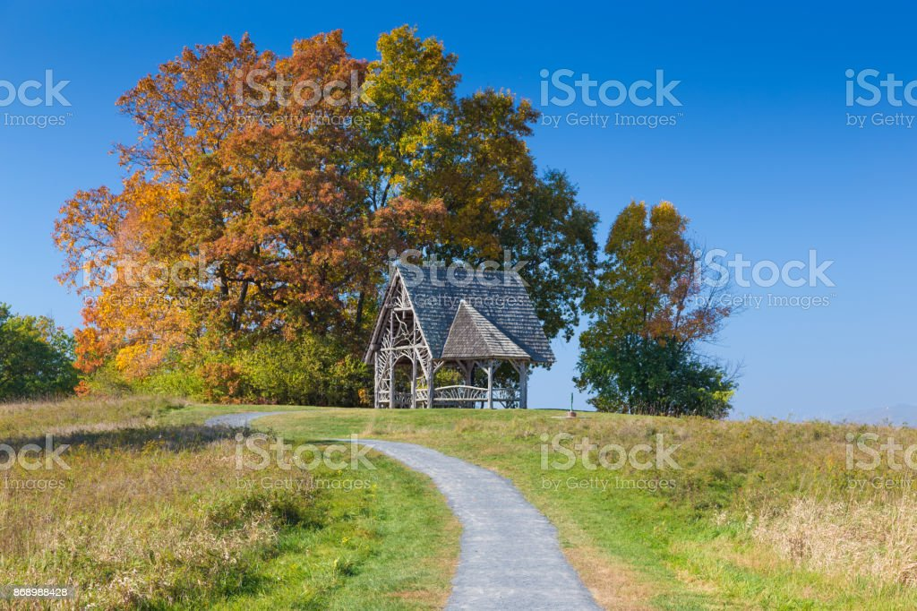 Landscape with Overlook Pavilion (Wooden Gazebo), Gravel Footpath, Trees in Autumn Colors (Foliage) and Vivid Blue Sky, Poets' Walk Park, Red Hook, Hudson Valley, New York. stock photo