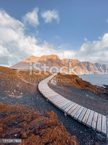 Landscape with picturesque wooden pathway through the rocky land and mountains on the background. Image made on mobile phone