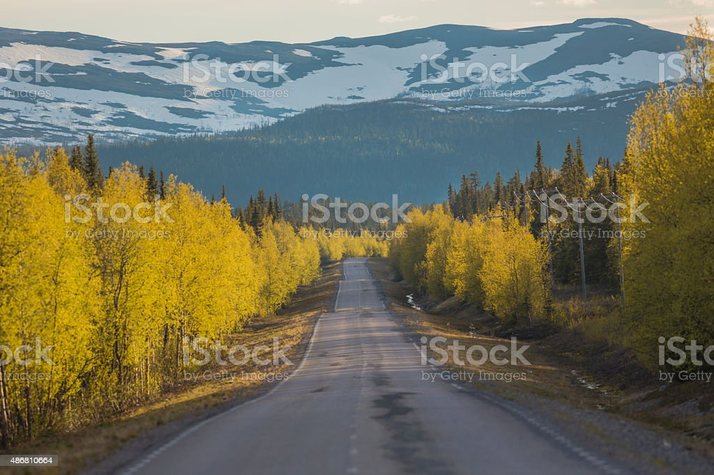 Landscape with road going straight and mountain in background stock photo