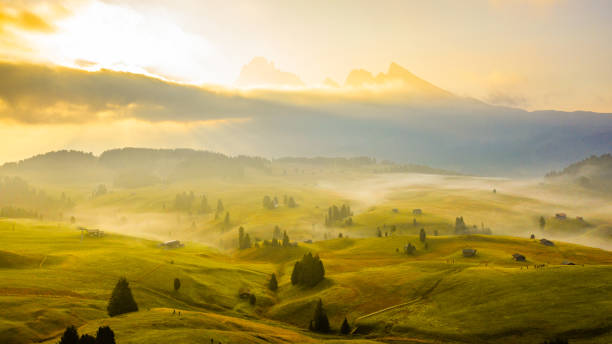 Landscape with rolling hills and mountains in fog at sunrise, Dolomites, Italy stock photo