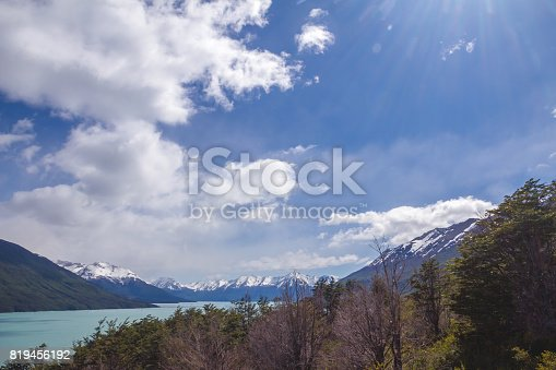 Landscape with snow covered mountains, Lago Argentino and beautiful cloudy sky during the sunny day. Hill with trees in front. Selective focus.