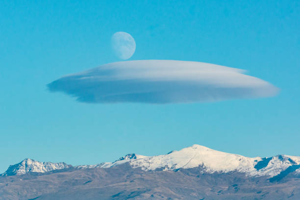 Landscape with the three important peaks of Sierra Nevada (Mulhacen, Veleta and Alcazaba) Landscape with the three important peaks of Sierra Nevada (Mulhacen, Veleta and Alcazaba) under a lenticular cloud with the crescent moon above the cloud. lenticular cloud stock pictures, royalty-free photos & images