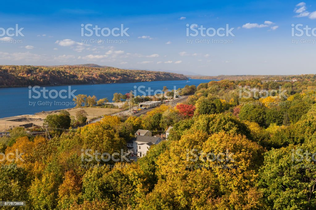 Landscape with Trees in Autumn Colors (Foliage), Hudson River, Railroad Track, Houses and Blue Sky, Poughkeepsie, Hudson Valley, New York. stock photo