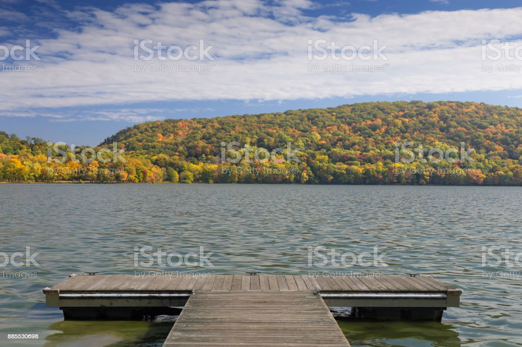 Landscape with Trees in Autumn Colors (Foliage), Pier and Blue Sky at Rockland Lake State Park, Hudson Valley, New York. stock photo