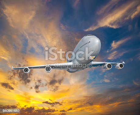 816320512 istock photo Landscape with white passenger airplane is flying in the blue sky with multicolored clouds at sunset. 940961652