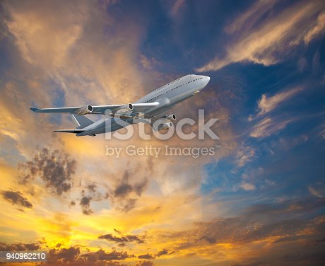 816320512 istock photo Landscape with white passenger airplane is flying in the blue sky with multicolored clouds at sunset. 940962210
